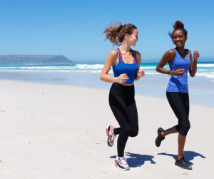 Two girl friends jogging on the beach smiling at one another